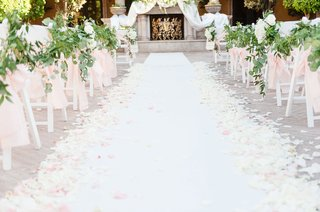 wedding-ceremony-outdoors-fireplace-mantel-at-altar-pink-ribbon-greenery-white-flower-petals