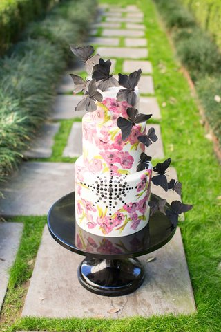 white-cake-with-pink-flower-design-and-black-jewels-and-black-butterflies-on-top-on-stone-path