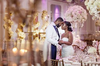 wedding-reception-at-castle-venue-groom-in-long-tail-tuxedo-tall-white-pink-centerpieces-gold-accent