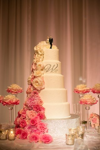 white-wedding-cake-with-silver-monogram-and-fresh-cascading-flowers
