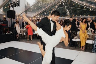 bride-in-one-shoulder-jumpsuit-for-first-dance-cool-lift-dance-lessons-groom-holding-bride-tent