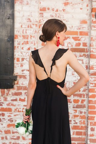 black-low-back-bridesmaid-dress-ruffle-strap-holding-white-flower-bouquet-red-earrings
