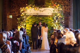 wedding-ceremony-jewish-wedding-new-york-green-backdrop-with-white-chuppah-ceiling-and-yellow-flower