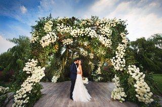 jewish-wedding-portrait-bride-groom-wood-aisle-under-greenery-white-flower-arch-chuppah-outdoor