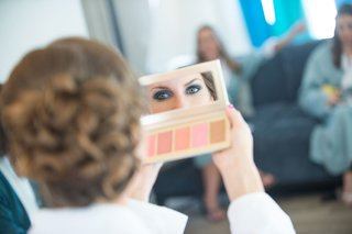 bride-looking-in-mirror-to-see-makeup