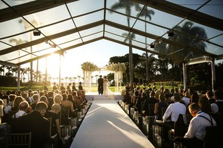 bride-and-groom-under-arch-acrylic-lucite-white-flowers-guests-in-gold-chairs-clear-top-tent-over