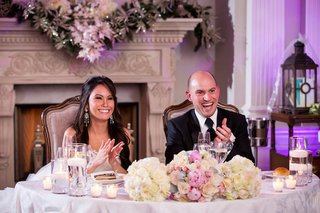 bride-with-chandelier-earrings-groom-in-a-black-tuxedo-sit-at-sweetheart-table-with-white-roses