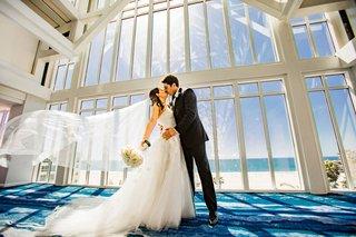 wedding-photo-bride-in-white-strapless-dress-kissing-groom-veil-blowing-in-wind-ocean-view-window