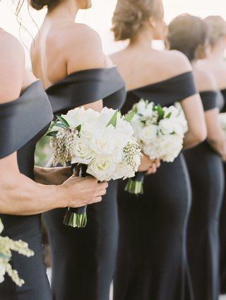 bridesmaids-holding-white-rose-bouquets-accented-with-greenery-off-shoulder-black-gowns