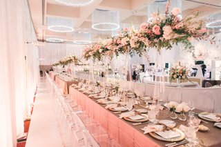 long-reception-table-with-tall-centerpiece-design-pink-flowers-leaves-white-flowers-glass-orbs