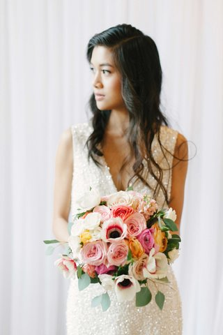 a-bride-in-a-shimmery-gown-holds-a-colorful-bouquet-of-white-pink-and-yellow-flowers-with-greenery