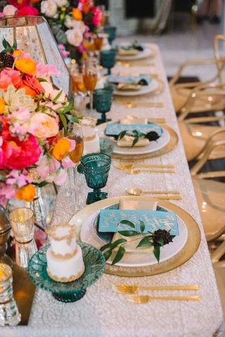 white-linen-gold-blue-plates-wedding-reception-pink-orange-flowers-blue-goblets