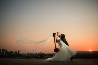 groom-in-armani-dips-bride-in-liancarlo-as-her-veil-blows-in-the-wind-at-sunset