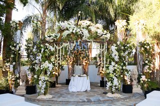 wedding-flower-arch-with-branches-green-leaves-white-roses-and-orchids