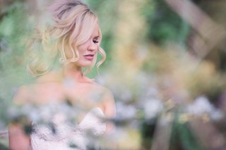 bride-with-blonde-curled-updo-hair-with-strapless-dress-and-pink-lipstick-eyelashes