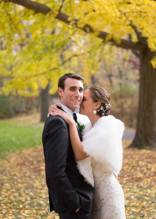 bride-in-a-lace-monique-lhuillier-gown-and-stole-hugs-groom-in-a-black-tuxedo