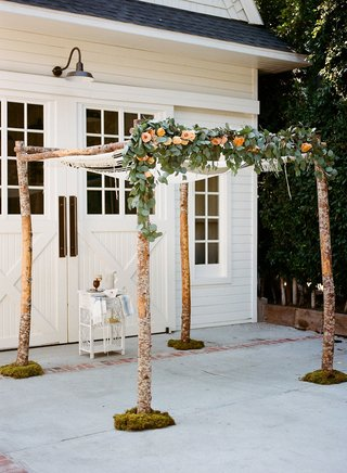 wedding-ceremony-arbor-chuppah-branches-with-greenery-and-peach-orange-rose-flowers