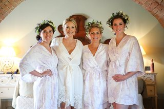bride-in-white-lace-trimmed-robe-bridesmaids-in-light-floral-robes-and-flower-crowns