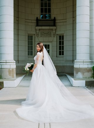bride-in-low-back-long-sleeve-wedding-dress-monique-lhuillier-long-hair-down-with-veil-white-bouquet