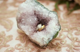 wedding-ring-gold-band-and-halo-engagement-ring-in-crystal-on-table-sequin-linens-reception