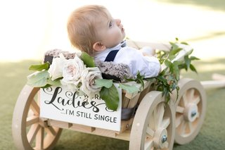 baby-ring-bearer-in-wooden-wagon-with-sign-reading-dont-worry-ladies-im-still-single