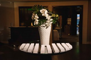 escort-card-table-white-vase-with-jungle-leaves-and-orchids-brentwood-country-club-carol-leifer
