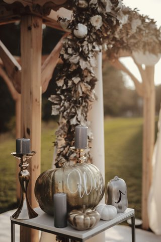 fall-wedding-ideas-wood-ceremony-arbor-gold-leaves-white-flowers-grey-candles-pumpkins-gold-white