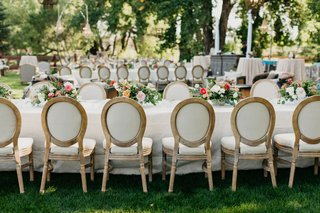 outdoor-garden-wedding-reception-oval-back-french-style-chairs-long-table-short-centerpieces-trees