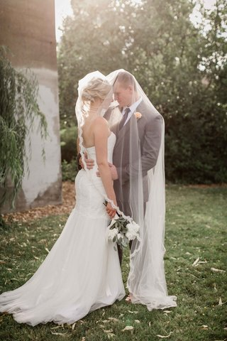 newlywed-couple-embracing-under-long-church-cathedral-veil-outdoor-portland-oregon-wedding-trumpet