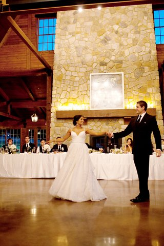 bride-is-lace-gown-dances-with-groom-in-a-black-suit-at-the-pavilion-at-orchard-ridge-farms-il