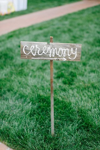 diy-wedding-ceremony-sign-in-cursive-font-on-rustic-wood