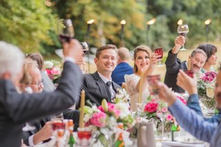 bride-and-groom-at-head-table-with-wedding-guests-toasts-colorful-goblets-pink-flowers-outdoor