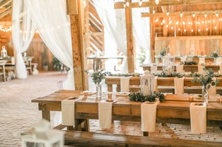 rustic-barn-wedding-wood-picnic-tables-and-benches-low-greenery-flower-arrangements-lanterns-white