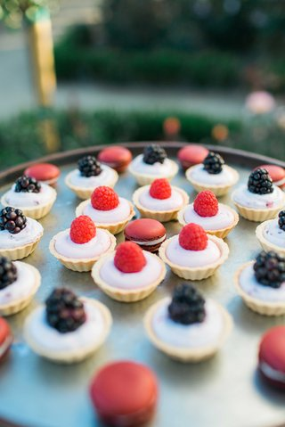 raspberry-and-blackberry-tart-desserts-with-red-french-macaroons-on-serving-tray