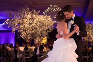 bride-in-a-strapless-monique-lhuillier-dress-with-pickup-skirt-dances-with-groom-in-black-tuxedo