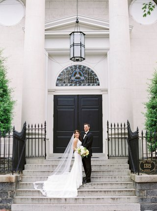 wedding-ceremony-church-venue-bride-in-wedding-dress-and-cathedral-renee-pawele-veil-with-groom-tux