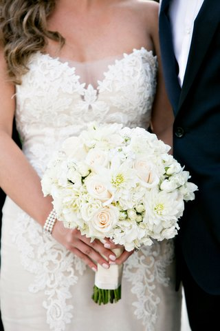 bride-in-ines-di-santo-wedding-dress-lace-with-pearl-bracelet-and-pink-manicure-white-bouquet-flower