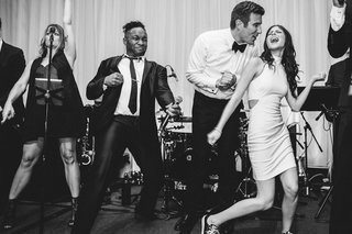 black-and-white-photo-of-bride-in-second-wedding-dress-and-groom-in-bow-tie-singing-and-dancing-band