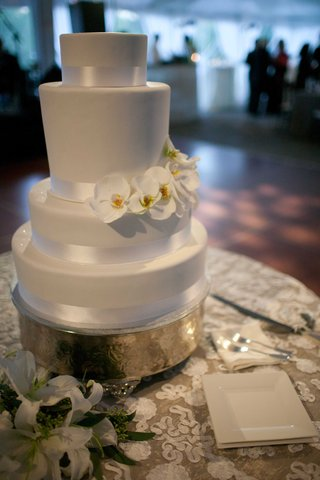 white-wedding-cake-with-fresh-white-flowers-on-gold-plate-and-white-lace-table-linens