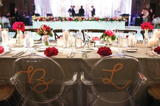 two-ghost-chairs-painted-in-a-gold-initial-at-wedding-head-table