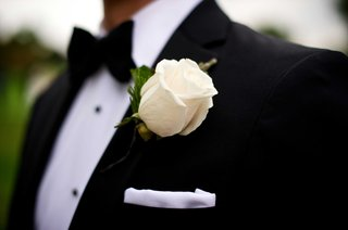 groom-in-black-tuxedo-bow-tie-white-pocket-square-rose-boutonniere