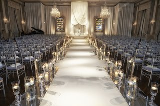 silver-wedding-ceremony-chairs-and-candlelit-aisle