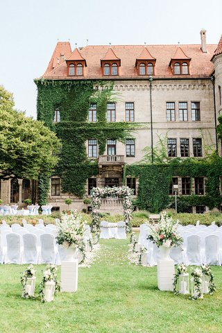 wedding-ceremony-germany-castle-venue-ivy-green-white-pink-flower-arrangements-white-chairs