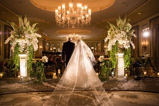 a-father-walks-daughter-bride-down-aisle-white-and-green-floral-arrangements-and-chandelier
