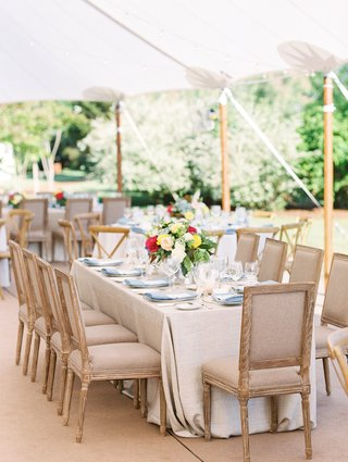 tent-wedding-reception-beige-wood-furniture-around-table-light-blue-linen-napkins-flowers-colorful