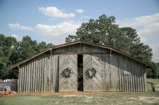 wedding-reception-barn-venue-sliding-barn-doors-with-wreaths-and-old-wood-siding-north-carolina