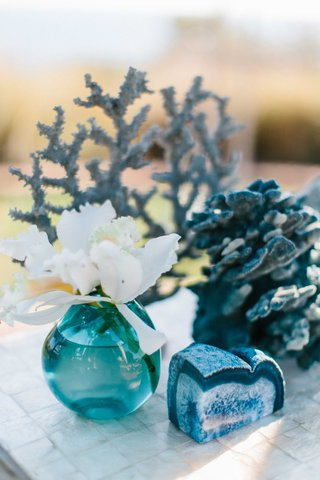 white-orchid-in-turquoise-bud-vase-blue-agate-slice-blue-coral-on-seashell-table-at-wedding