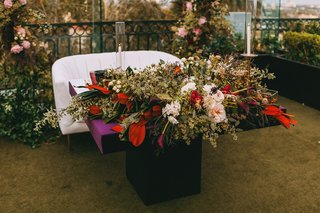 sweetheart-table-with-banquette-settee-purple-table-with-lush-foliage-arrangement