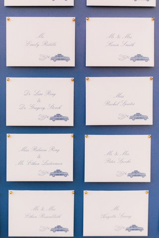 blue-board-with-escort-card-calligraphy-taxi-theme-find-your-seat-gold-push-pins-transportation