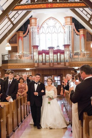 bride-walks-down-aisle-on-arm-of-brother-at-church